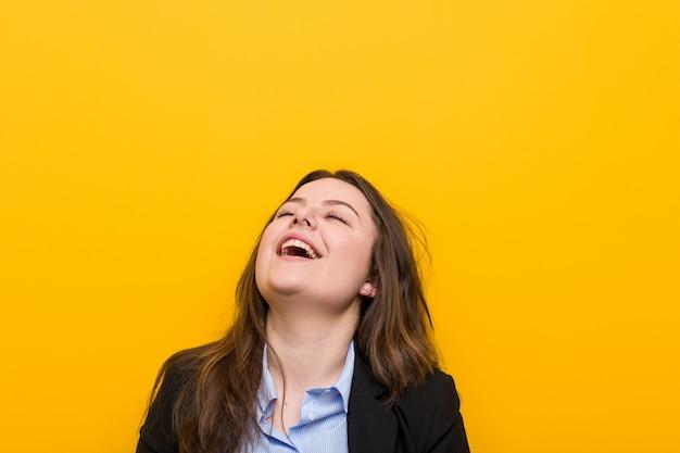 若いプラスサイズの白人ビジネス女性リラックスして幸せな笑い、歯を見せて首を伸ばした。