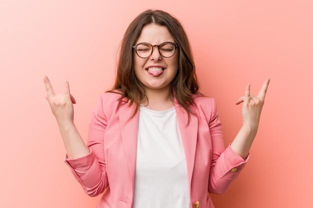 指で岩ジェスチャーを示す若いプラスのサイズのビジネス白人女性