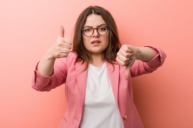 親指アップと親指ダウン、難しい選択を示す若いプラスのサイズのビジネス白人女性