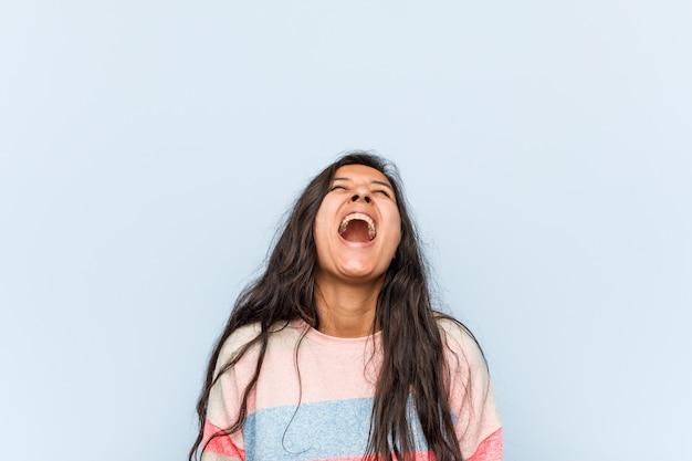 Молодой модный индийский женщина расслабился и счастливый смех, шея растянута, показывая зубы.
