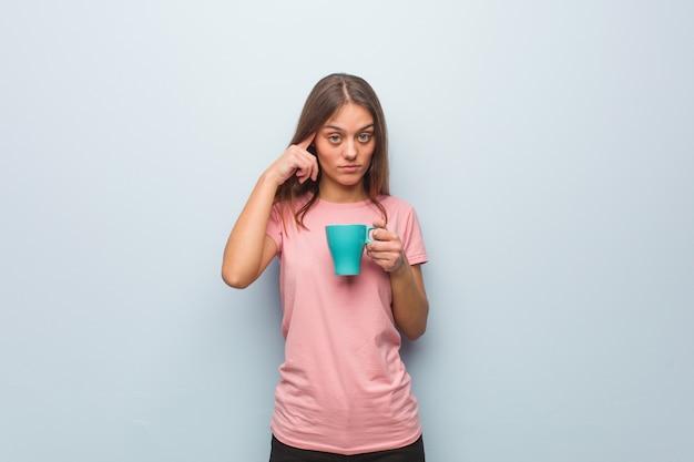 アイデアを考えて若いかなり白人女性。彼女はマグカップを持っています。
