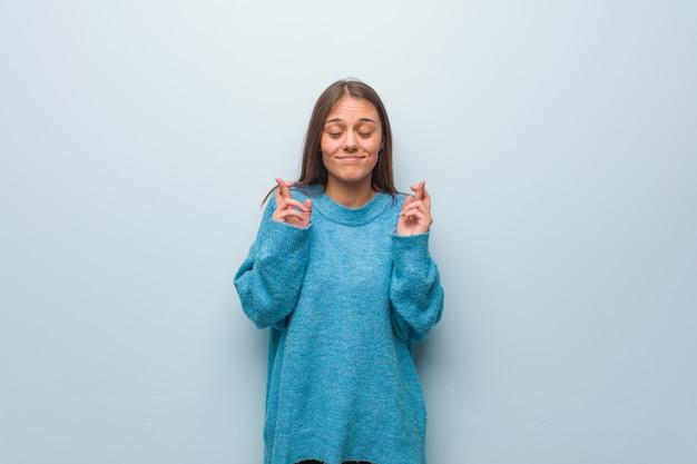 運を持っているための指を交差青いセーターを着ている若いきれいな女性