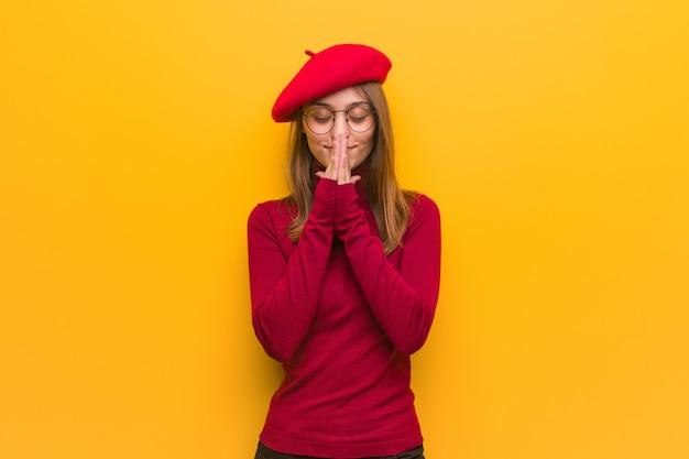 非常に幸せと自信を持って祈る若いフランス人アーティストの女性