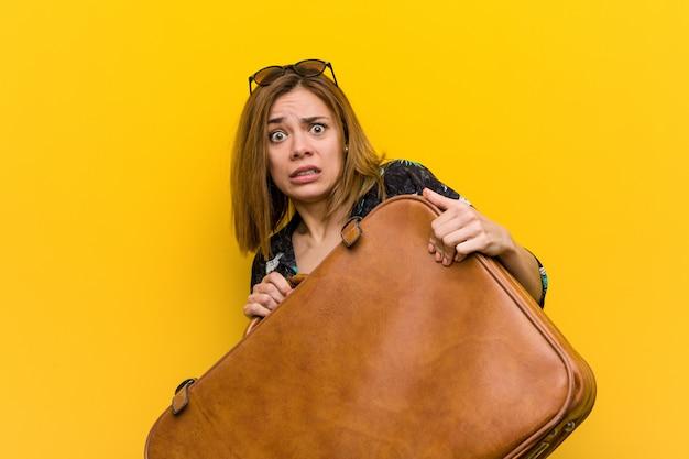 レザーバッグを保持している若い女性は彼女の休暇を怖がって、彼女は飛ぶために偏見を持っています。