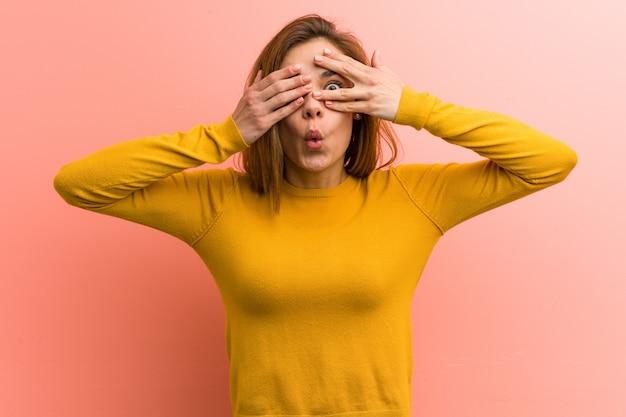 若いかなり若い女性はおびえたと神経質の指の間で点滅します。