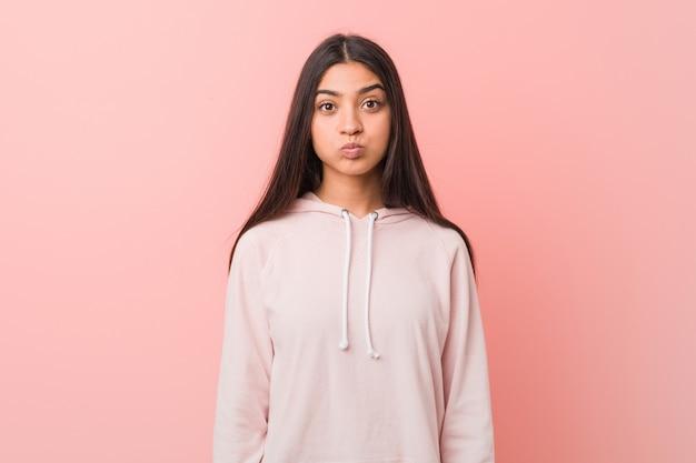 Молодая симпатичная арабская женщина, одетая в непринужденный спортивный вид, дует в щеки, устала выражением выражение лица .