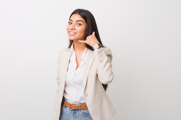 指で携帯電話のジェスチャーを示す白に対して分離された若いビジネスアラブ女性。