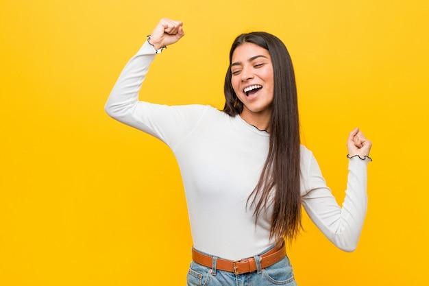 Молодая милая арабская женщина против желтого поднимая кулака после победы, победителя.