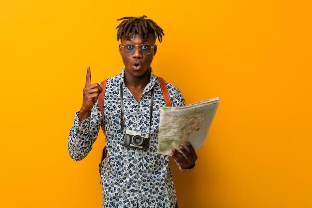 創造性のいくつかの素晴らしいアイデアを持つマップを保持している若いラスタ黒人。