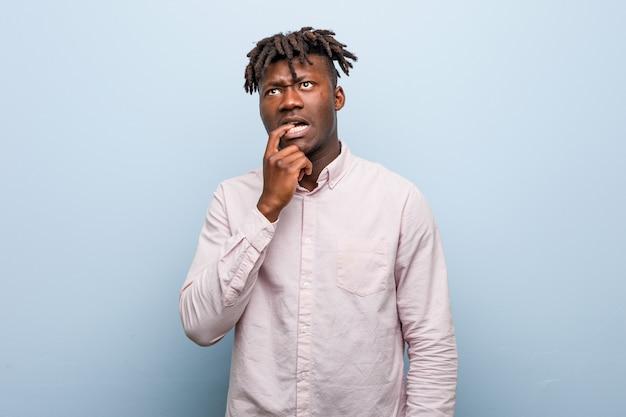 若いビジネスアフリカ黒人男性は、コピースペースを見て何かについて考えてリラックスしました。