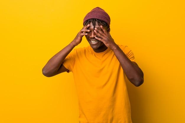おびえた、緊張した指の間で黄色の瞬きにラスタスを着た若い黒人男性。