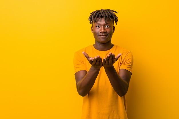 カメラに提供している手のひらで何かを保持している黄色のラスタスを着ている若い黒人男性。