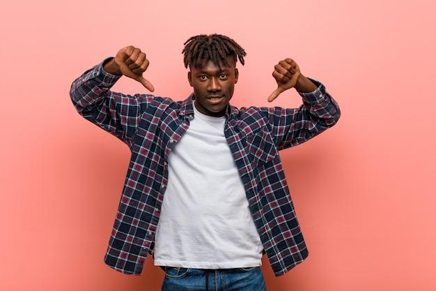 Молодой африканский чернокожий человек показывая большой палец руки вниз и выражая нелюбовь.