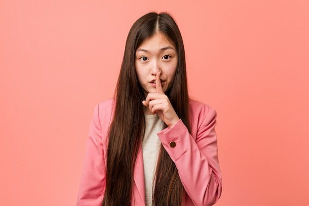 秘密を守るか沈黙を求めるピンクのスーツを着ている若いビジネス中国の女性。