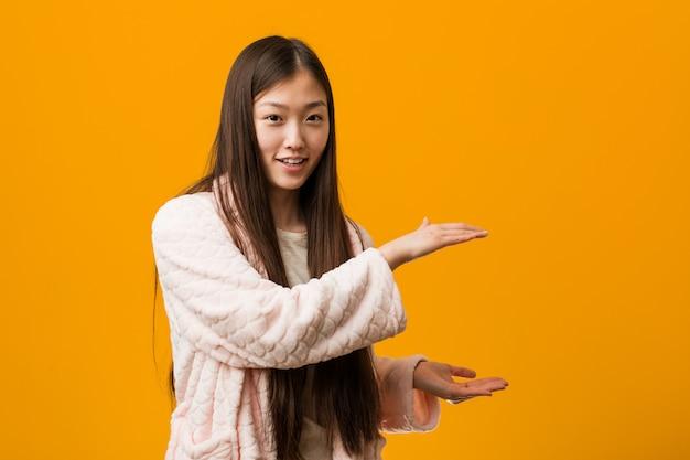 パジャマの若い中国人女性は、両手でコピースペースを保持していることにショックと驚きを覚えました。