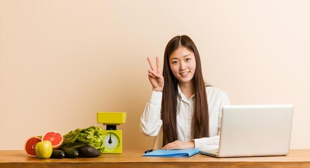 若い栄養士の中国人女性が勝利のサインを示し、広く笑顔の彼女のラップトップで働いています。