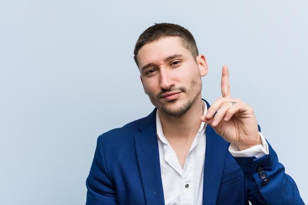 指でナンバーワンを示す若いビジネス白人男。