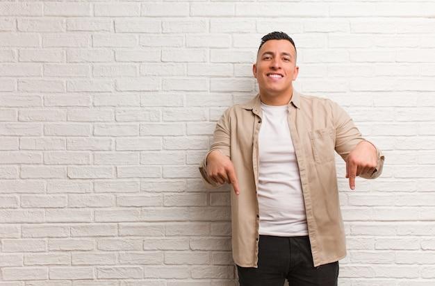 指で下を指している若いラテン男