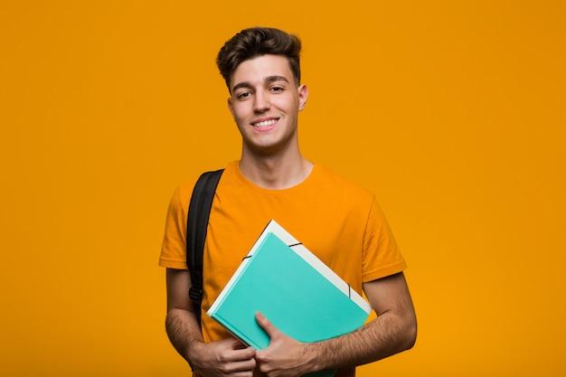 Молодой студент мужчина держит книги, улыбаясь и поднимая большой палец вверх