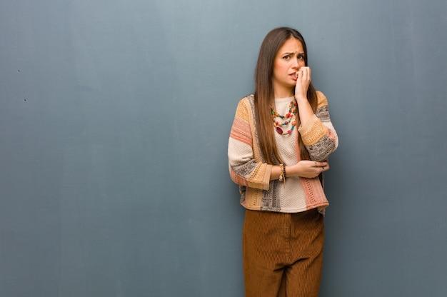 Молодая хиппи женщина кусает ногти, нервничает и очень беспокоится