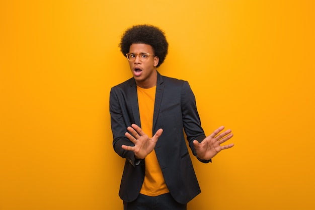 嫌悪感のジェスチャーをしている何かを拒否するオレンジ色の壁の上の若いビジネスアフリカ系アメリカ人
