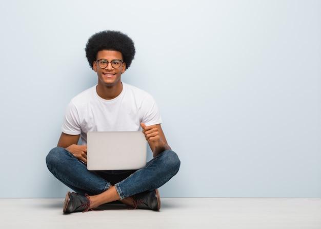 Молодой черный человек, сидя на полу с ноутбуком веселый с большой улыбкой