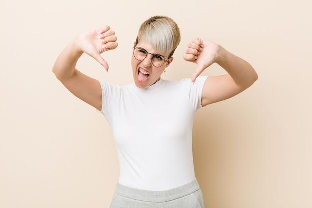 Молодая подлинная естественная женщина нося белую рубашку показывая большой палец руки вниз и выражая нелюбовь.