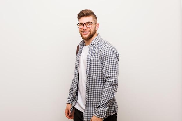 若い現代ビジネスの男は、笑みを浮かべて、陽気で快適な脇に見えます。
