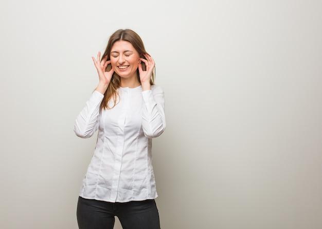 ロシアの少女の手で耳を覆う