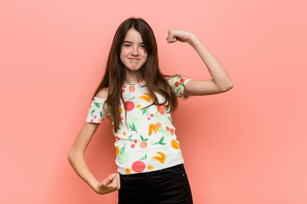 勝利、勝者の後に拳を上げる赤い壁に夏の服を着ている少女。