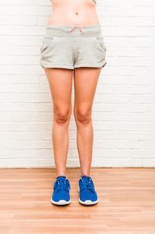 脚の若い白人のスポーティな女性