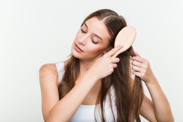 彼女の髪をブラッシング若い白人女性