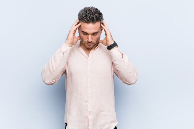 寺院に触れると頭痛を持っている若いハンサムなクールな男。