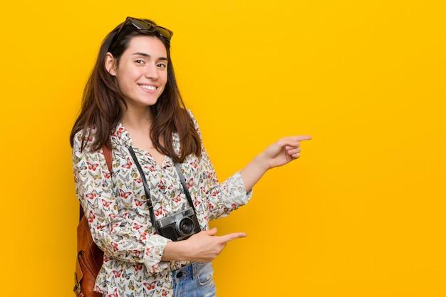 若いブルネット旅行者の女性は、人差し指で離れて指している興奮しています。