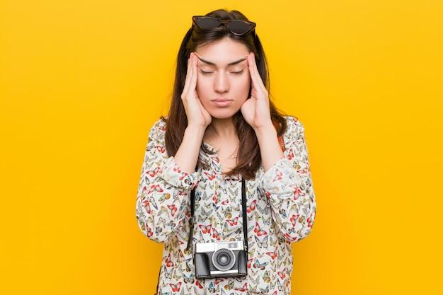 寺院に触れると頭痛を持つ若いブルネット旅行者女性。