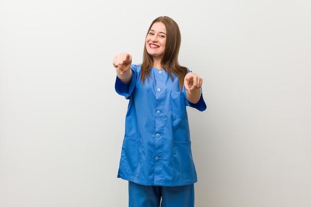 白い壁の陽気な笑顔を指す若い看護婦さん女性。