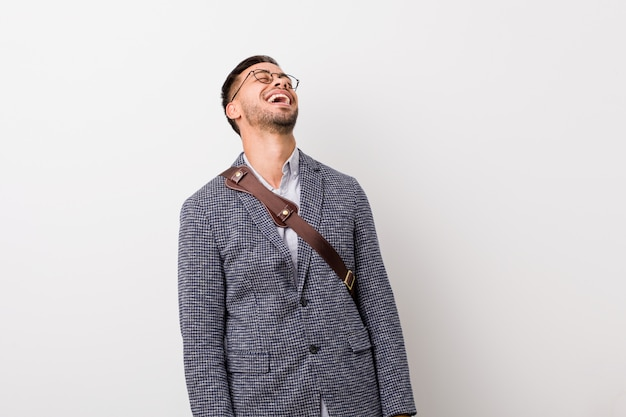 白い壁の若いビジネスフィリピン人はリラックスして幸せな笑い、首を伸ばして歯を見せています。