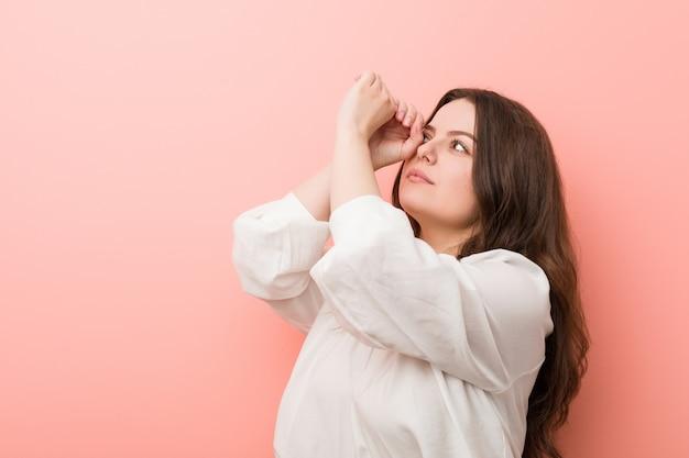 ピンクに対して立っている若い白人曲線の女性