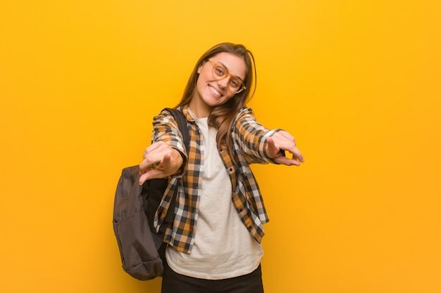 陽気な笑顔のポインティングフロントの若い学生女性
