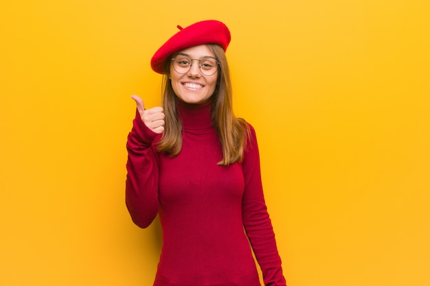 若いフランス人アーティストの女性の笑顔と親指を上げる