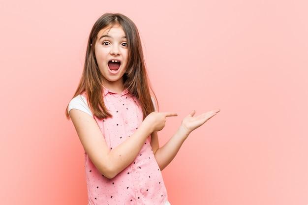 かわいい女の子は、手のひらを保持して興奮しています。