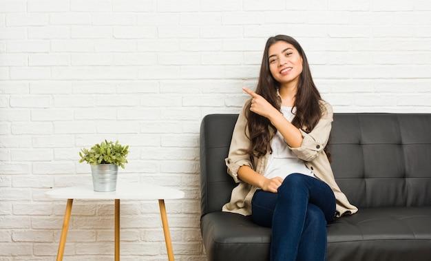 Молодая арабская женщина, сидя на диване, улыбаясь и указывая в сторону, показывая что-то пустое пространство.
