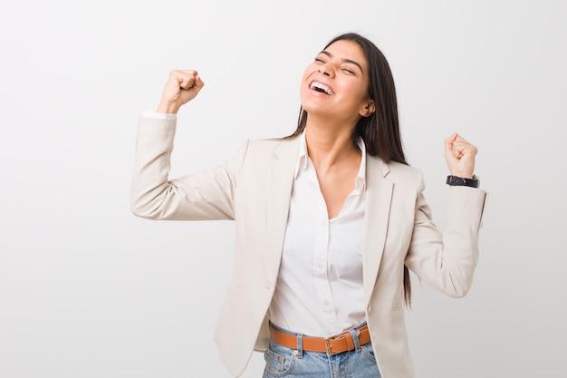 勝利、勝者の後拳を上げる白に対して分離された若いビジネスアラブ女性。