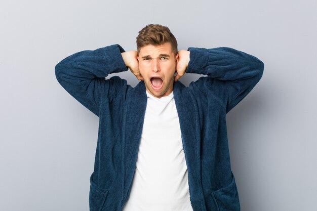 あまりにも大きな音が聞こえないようにしようと手で耳を覆うパジャマを着ている若い白人男。
