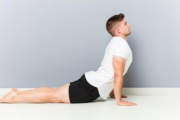 ヨガの練習を伸ばす若い白人男。