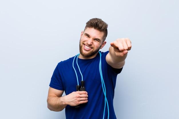 Молодой кавказский спортсмен с улыбками скакалки жизнерадостными указывая к фронту.