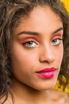 若いアフリカ系アメリカ人の美しいとメイクアップ女性がポーズのクローズアップ
