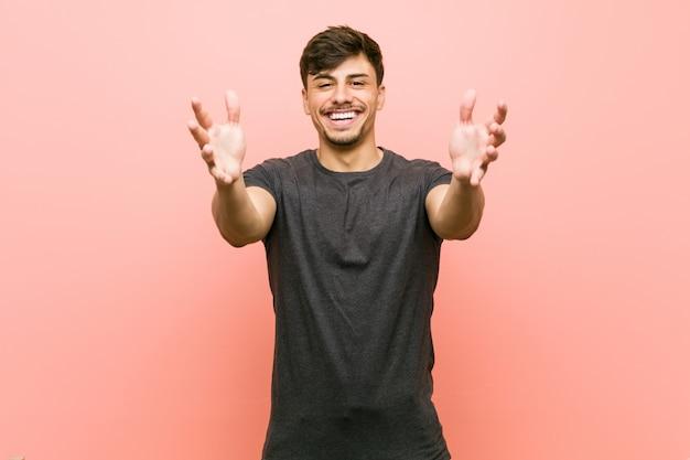 若いヒスパニック系のカジュアルな男は、カメラに抱擁を与えると確信しています。
