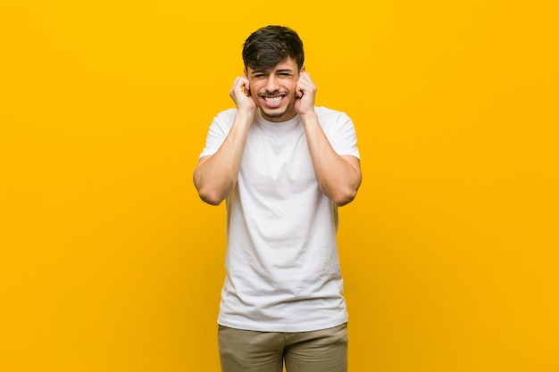 若いヒスパニック系のカジュアルな男の手で耳を覆っています。