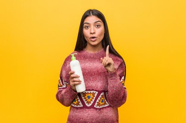 創造性のいくつかの素晴らしいアイデアを持つクリームボトルを保持している若いアラブ女性。